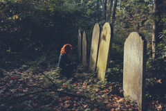 Grieving woman by grave. A grieving woman dressed in black is sitting by a grave Stock Photo