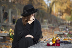 Grieving woman at graveyard. Woman in deep sorrow dressed in black at graveyard Stock Images