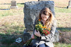 Grieving woman sitting at gravestone. Sad and somber lady dressed in black coat,sitting with flowers at gravestone of lost loved one Stock Photos