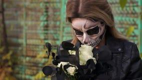 Griezelige bruid met een boeket van zwarte bloemen en samenstelling in de vorm van een schedel stock videobeelden