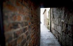 Griezelige en griezelige donkere baksteensteeg of verborgen passage die tot het licht in het Verenigd Koninkrijk leiden Royalty-vrije Stock Foto