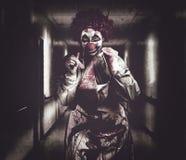 Griezelige medische clown in de gang van het grungeziekenhuis Royalty-vrije Stock Fotografie