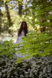 Griezelige vrouw in lange witte kleding die zich in een bos bevinden Stock Afbeeldingen
