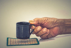 Griff des alten Mannes Handmit schwarzer Schale auf der weißen Tabelle Lizenzfreie Stockfotografie