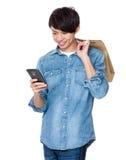 Griff des jungen Mannes mit Einkaufstasche und Blick auf das Mobiltelefon Stockbild