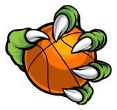 Griffe de monstre ou d'animal tenant la boule de basket-ball Photographie stock libre de droits