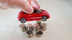 Griffe in seinem kleinen roten Spielzeug Fiats 500 der Finger über Stapel von ein-israelischen Schekel-Münzen stockbilder