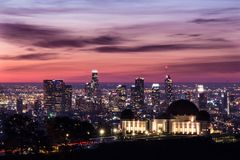 Griffith Park Observatory in front on downtown Los Angeles at sunrise. Stock Photos