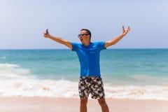 Griffmobiltelefon des jungen Mannes machen Foto der panoramischen Ansicht des Sommerstrandes See Lizenzfreie Stockfotos