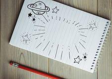 Griffonnage de l'espace sur le bloc-notes à côté du crayon rouge photo stock