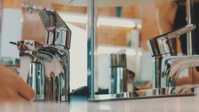 Grifo abierto de la chica joven del fregadero en espejo delantero en cuarto de baño Agua Mañana almacen de video