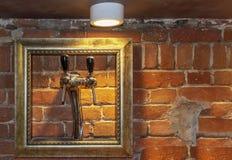 Grifo de la barra para la cerveza que dispensa, en un marco de madera, contra una pared de ladrillo roja fotos de archivo libres de regalías