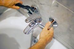 Grifo del baño de la fijación del fontanero con una llave ajustable fotos de archivo