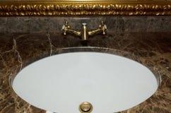 Grifo del estilo del vintage del metal del oro en un cuarto de baño fotografía de archivo