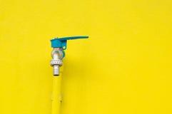 Grifo del primer en fondo amarillo concreto de la pared Imagen de archivo