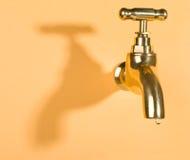 Grifo en pared anaranjada con gota del agua foto de archivo