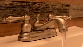 Grifo rústico del cuarto de baño con el fondo de madera resistido de la mañana del fondo de la pared fotos de archivo libres de regalías