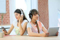 Grifriends spending time using electronical devices. Girl friends connected each one with a different support Stock Images