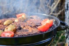 Grigli il cuoco unico che aggiunge la salsa e l'alimento sulla griglia calda Fotografia Stock