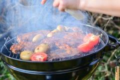 Grigli il cuoco unico che aggiunge la salsa e l'alimento sulla griglia calda Immagini Stock Libere da Diritti