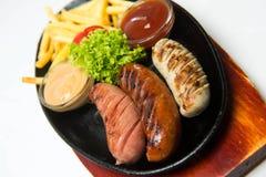 Grigli le salsiccie sul piatto di legno con le patate fritte e le salse Priorità bassa bianca Fotografia Stock