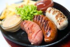 Grigli le salsiccie sul piatto di legno con le patate fritte e le salse Priorità bassa bianca Fotografia Stock Libera da Diritti