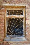 Griglia arrugginita di sicurezza del ferro sulla finestra rotta in rovinato in abbandonato Fotografia Stock