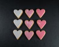 Griglia dei biscotti glassati del cuore sul nero Fotografia Stock Libera da Diritti