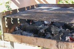 Griglia del barbecue che ottiene infornata su fotografie stock