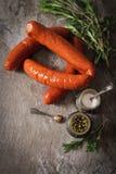 griglia del bratwurst con i rosmarini del pepe e del sale Immagini Stock