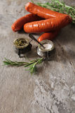 griglia del bratwurst con i rosmarini del pepe e del sale Fotografia Stock