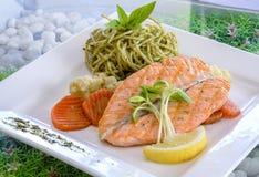 Griglia della bistecca di color salmone servita con la pasta di pesto Fotografia Stock Libera da Diritti