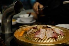 Griglia della carne di maiale sulla pentola dell'ottone del BBQ immagini stock libere da diritti