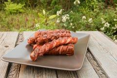 Griglia della salsiccia Su un vassoio Giardino Immagine Stock