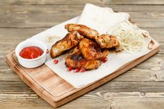 Griglia delle ali di pollo Servendo su un bordo di legno su una tavola rustica Menu del ristorante con barbecue, una serie di fot immagine stock