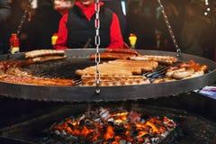 Grigliando le salsiccie tedesche tipiche in un mercato si bloccano Fotografia Stock