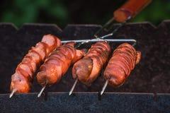 Grigliare le salsiccie sulla griglia del barbecue Immagini Stock