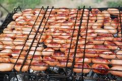 Grigliare le salsiccie sulla griglia del barbecue Fuoco selettivo Immagini Stock Libere da Diritti