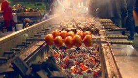 Grigliare pomodoro e carne sugli spiedi Ristorante all'aperto della griglia archivi video