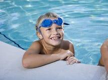 Grijnzen van de jongen, die op kant van zwembad hangt royalty-vrije stock afbeeldingen