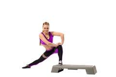 Grijnzend meisje die gestalte gevend oefening op stepper doen Stock Afbeelding