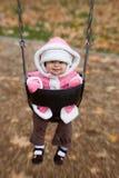 Grijnzende baby op de schommelingsreeks Royalty-vrije Stock Fotografie