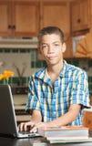 Grijnzende tiener met laptop en handboeken Stock Foto