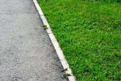 Grijs asfalt en groene grasgrens in perspectief Royalty-vrije Stock Afbeelding