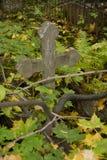 Grijs concreet eenvoudig Orthodox Christelijk kruis op een oude de herfstbegraafplaats stock foto's