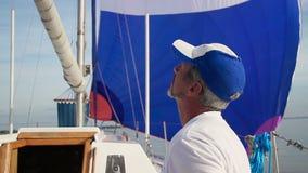 Grijs-haired kapitein die orden geven aan bemanning op varend jacht stock video