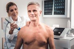 Grijs-haired mens die aan chiropracticus voor raad komen royalty-vrije stock fotografie