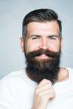 Grijs-haired mens die baard trekken royalty-vrije stock afbeeldingen