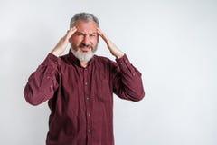 Grijs-haired mens met een baard die aan wanhopig en beklemtoonde hoofdpijn lijden omdat pijn en migraine stock foto