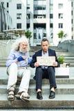 Grijs-haired verworpen mensenzitting dichtbij geval met persoonlijke bezittingen royalty-vrije stock foto's